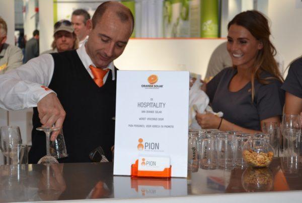 PION horeca promotie uitzendbureau Bergen op Zoom Personeel collega meewerken medewerker op beur met oranje Soler drankje hospitality